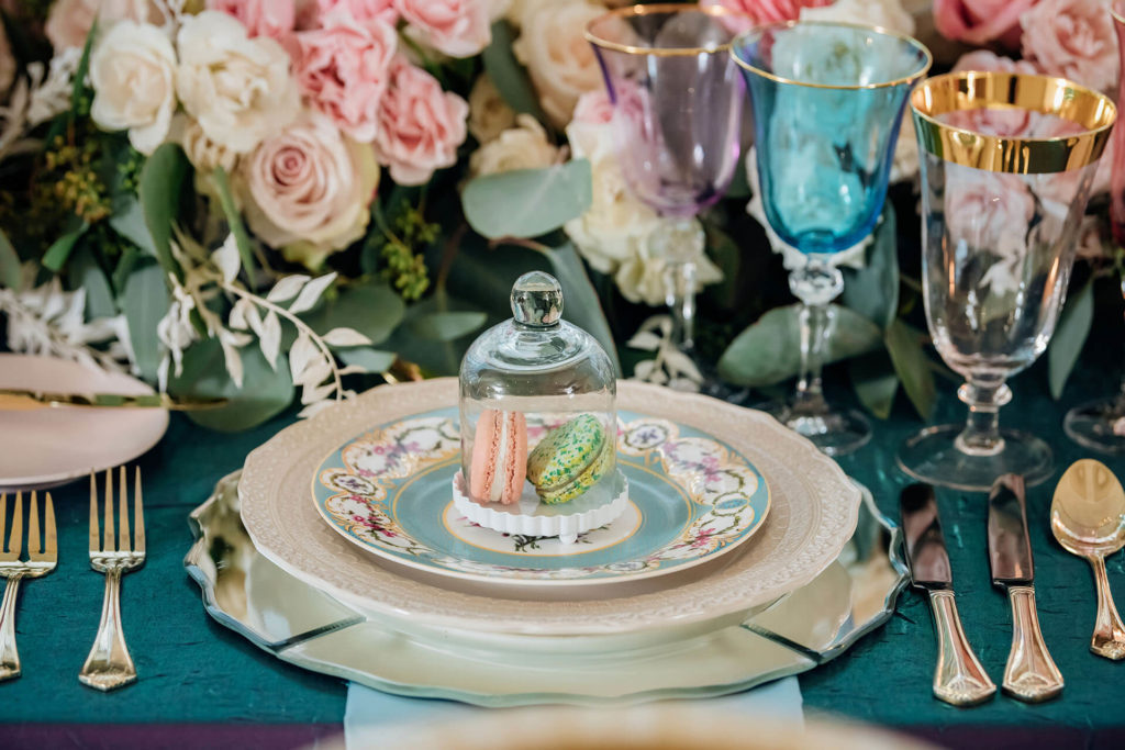Reception place setting for one. Beautiful multi-color floral centerpiece and glasses. Gold cutlery and patterned dishes with two macarons on top under glass display.