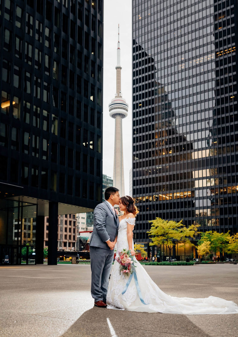 Downtown Toronto wedding photo with a bride and groom facing each other and holding hands framed by two large office towers and the stunning CN Tower in the background.