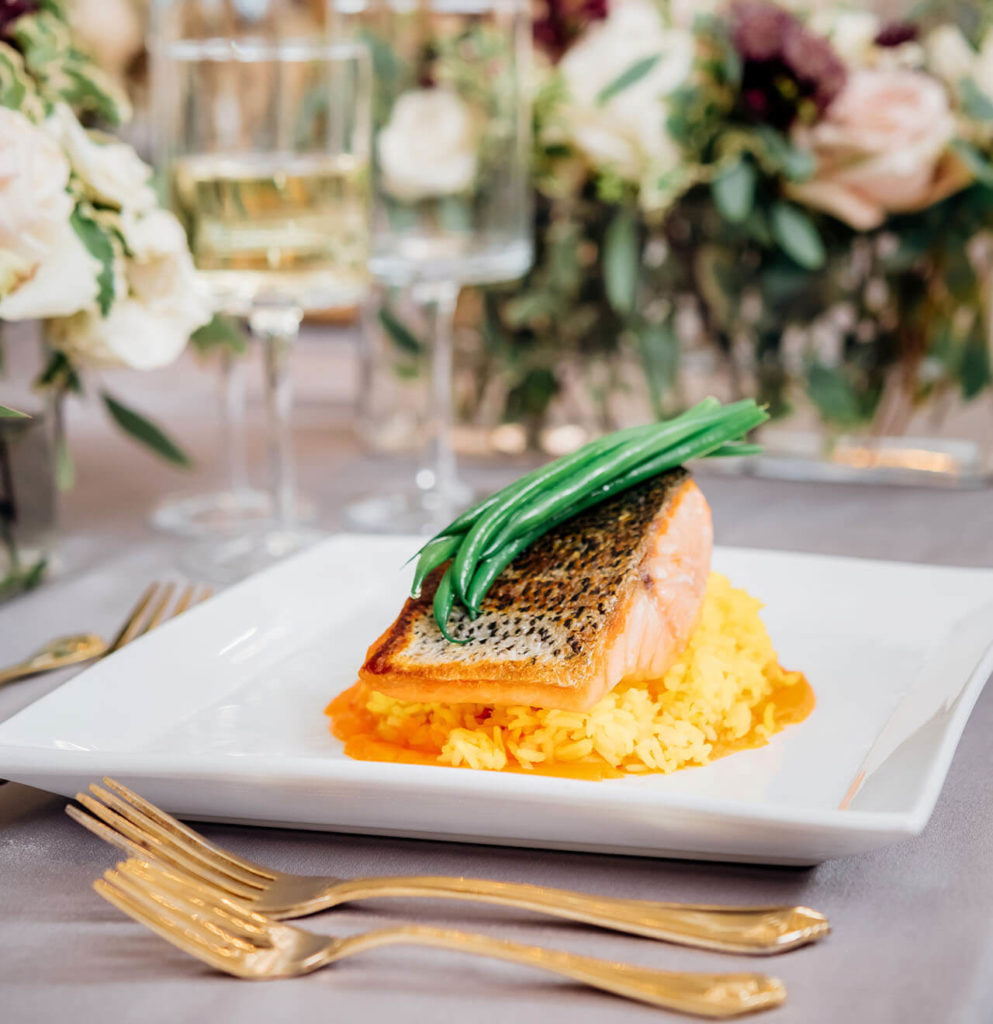 Perfectly prepared plated salmon on top of a bed of risotto with a decadent cream sauce and fresh green beans. The background has beautiful burgundy and rose colored flower arrangements and wine glasses.