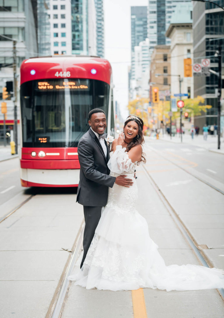 Downtown Toronto wedding photo with a bride and groom standing in front of a streetcar on King Street.