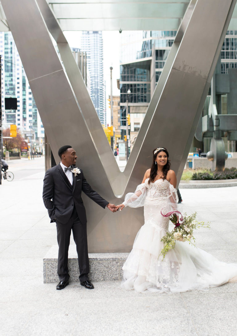 Downtown Toronto wedding photo with a bride and groom holding hands in front of a large V.