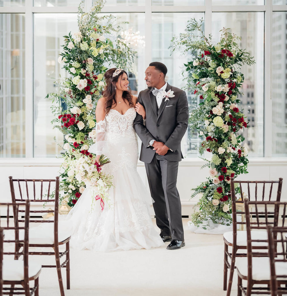 Bride and groom standing in front of a stunning seven-foot-tall floral backdrop with big, bright windows in the background. This is where they will commit to forever together.