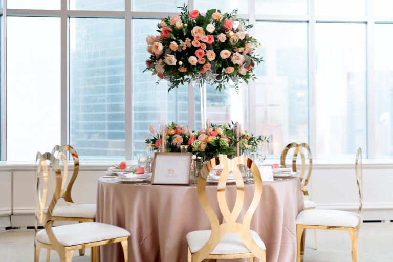 Wedding guest table, with a rose-colored tablecloth and beautiful floral center piece composed on various shades of pink flowers set in front of large windows.