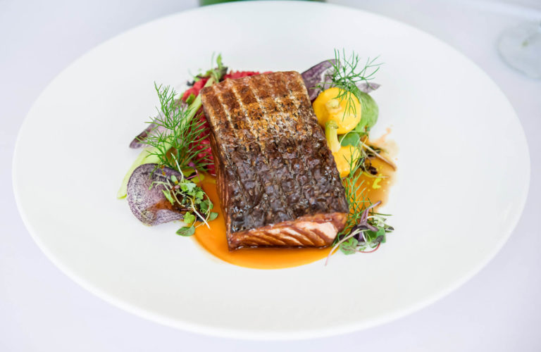 A plate with mouth watering smoke roasted salmon with fennel pollen truffle carrot purée, baby squash, red beet risotto, and Peruvian potato chips.