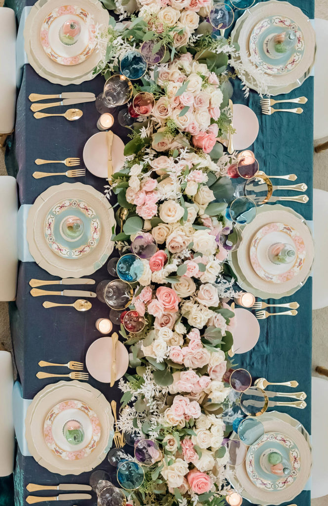 Beautiful, whimsical wedding reception head table setting in a top-down view. It features a shimmery, iridescent, turquoise table covering, with lovely pastel-coloured flowers and opulent china.