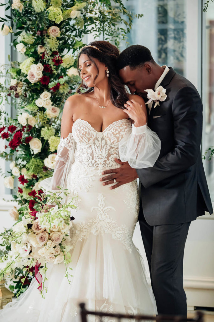 A Groom is standing behind his bride with his arms around her, giving her a kiss on her shoulder. The bride is absolutely glowing in front of a gorgeous floral arrangement that is so big, it is taller than her.