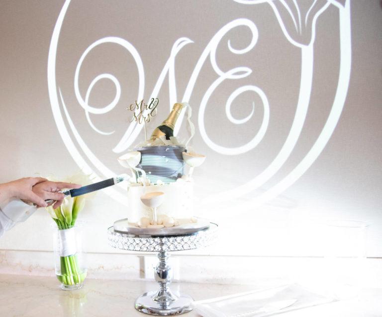 Wedding cake set in front of a beautiful custom LED monogram.